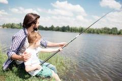 Ein Bild von den Jungen, die zusammen am Rand von See und von Fischerei sitzen Junge hält lange Fischstange, während sein Vati is Stockfotografie