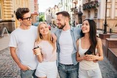 Ein Bild von den schönen zusammen stehenden und aufwerfenden Leuten Blondes Mädchen lächelt auf Kamera und hält Tasse Kaffee Stockbilder