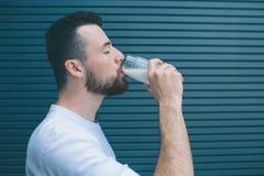 Ein Bild von Trinkmilch des Mannes vom Glas Er hält Augen geschlossen Lokalisiert auf gestreiftem und blauem Hintergrund stockbild