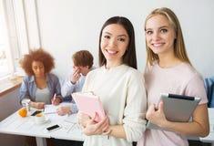 Ein Bild von zwei schönen asiatischen stehenden und lächelnden Mädchen Brunette hält ein rosa Notizbuch, während das blonde Mädch Lizenzfreie Stockbilder