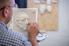 Ein Bildhauer sculpts eine Skulptur eines Person ` s Gesichtes Horizontaler Rahmen Lizenzfreies Stockbild