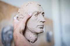 Ein Bildhauer sculpts eine Skulptur eines Person ` s Gesichtes Horizontaler Rahmen Stockfotografie