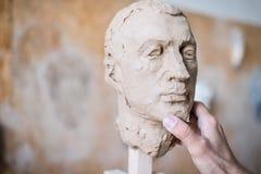 Ein Bildhauer sculpts eine Skulptur eines Person ` s Gesichtes Horizontaler Rahmen Stockfotos