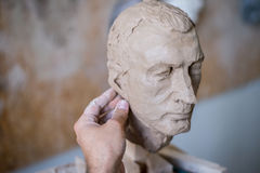 Ein Bildhauer sculpts eine Skulptur eines Person ` s Gesichtes Horizontaler Rahmen Lizenzfreie Stockfotografie
