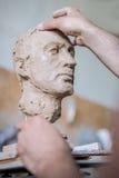Ein Bildhauer sculpts eine Skulptur eines Person ` s Gesichtes Horizontaler Rahmen Lizenzfreie Stockfotos