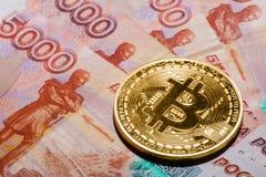 Ein Bitcoin auf Banknoten der russischen Rubel Stockfotografie