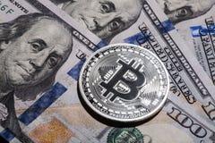 Ein Bitcoin auf hundert Dollarscheinen Stockfotografie