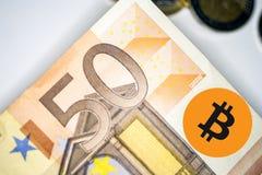 Ein bitcoin mit Euromünzen lizenzfreie stockfotos