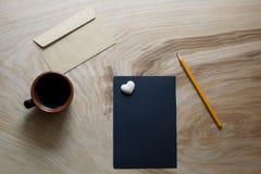 Ein Blatt des dunklen Papiers, Umschlag, Tasse Kaffee auf einer hölzernen Beschaffenheit Lizenzfreies Stockbild
