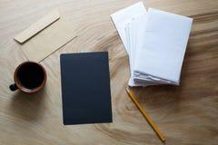 Ein Blatt des dunklen Papiers, Umschlag, Tasse Kaffee auf einer hölzernen Beschaffenheit Stockbild