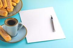 Ein Blatt des Wei?buches ist auf einem blauen Hintergrund mit einem Tintenstift leer Kopieren Sie Platz lizenzfreie stockfotos