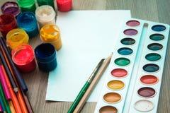 Ein Blatt Papier, Bleistifte und Farben Stockbilder