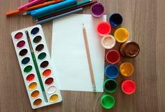 Ein Blatt Papier, Bleistifte und Farben Stockfotografie