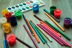 Ein Blatt Papier, Bleistifte und Farben Lizenzfreie Stockfotos