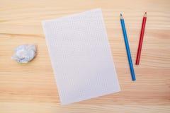 Ein Blatt Papier und Bleistifte auf dem Holztisch Platz für das Zeichnen oder das Schreiben Lizenzfreie Stockfotografie
