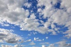 Ein blauer bewölkter Himmel mit vielen kleinen Wolken, welche die SU blockieren Lizenzfreies Stockfoto