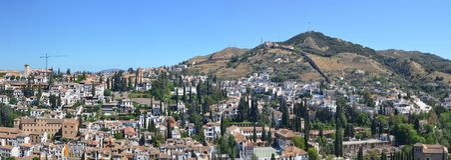 Ein blauer Frühlingshimmel über Spanisch-Granada-Stadtdächern stockfotos