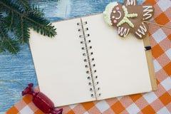 Ein blauer hölzerner Weihnachtshintergrund mit einem Notizbuch Stockfotografie