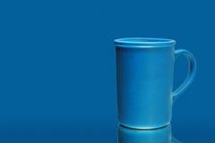 Ein blauer keramischer Becher über einem blauen Hintergrund Stockbild