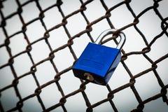 Ein blauer Liebes-Verschluss padlocked zu einem Zaun stockbild