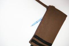 Ein blauer Stift wird aus einer braunen Bleistifttasche auf einem weißen backgro heraus genommen Stockbild