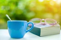 Ein blauer Tasse Kaffee mit unscharfen Brillen und geöffnetem Buch Lizenzfreies Stockbild