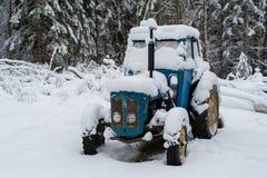Ein blauer Traktor bedeckt im Schnee lizenzfreie stockbilder