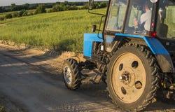 Ein blauer Traktor mit einem Anhänger für Landarbeitfahrten entlang einer Straße auf einem Weizengebiet lizenzfreies stockfoto