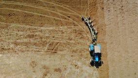 Ein blauer Traktor mit vier Ploughshares pflügt trockenes fruchtbares Land der braunen Farbe Das Konzept der Landwirtschaft, Lan stock video
