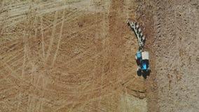 Ein blauer Traktor mit vier Ploughshares pflügt trockenes fruchtbares Land der braunen Farbe Das Konzept der Landwirtschaft, Land stock footage