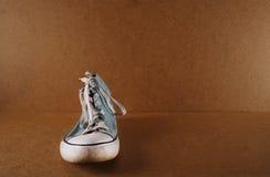 Ein blauer Turnschuh auf einem hölzernen Hintergrund Stockfotos