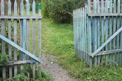 Ein blaues altes zackiges Tor zu einem Datschagarten in einem Dorf mit Boden und Gras und Bäume Lizenzfreies Stockfoto