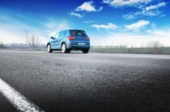 Ein blaues Auto auf der Landschaftsstraße gegen Himmel mit Wolken lizenzfreies stockbild