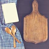Ein blaues Geschirrtuch und ein Notizbuch auf einem dunklen hölzernen Hintergrund Menü, Platz für Text, Rezept lizenzfreie stockfotos