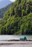 Ein blaues Zelt auf dem Ufer von einem Gebirgssee stockbild