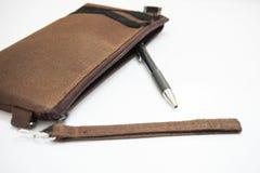 Ein Bleistift wird aus brauner Bleistifttasche auf einem weißen Hintergrund heraus genommen Lizenzfreies Stockbild