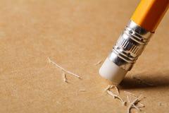 Ein Bleistiftradiergummi, der einen schriftlichen Fehler auf einem Blatt Papier entfernt Stockbild