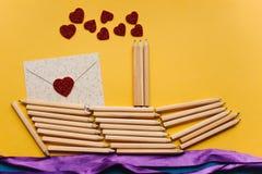 Ein Bleistiftschiff und ein Buchstabe mit einem Herzen Kreativer Arbeitsplatz Vorbereiten für den Feiertag Stockbild