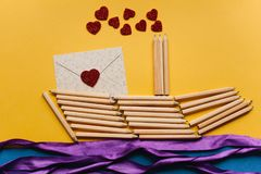 Ein Bleistiftschiff und ein Buchstabe mit einem Herzen Kreativer Arbeitsplatz Vorbereiten für den Feiertag Stockfotografie