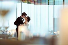 Ein Blick von den Glaswaren auf einer küssenden Hochzeitspaarstellung I Stockbilder