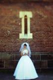 Ein Blick von fern auf einer Braut, die unter einem kleinen Fenster steht Stockbilder