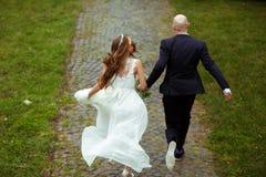 Ein Blick von hinten auf den laufenden Hochzeitspaaren Lizenzfreie Stockbilder