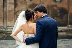 Ein Blick von hinten auf einem Bräutigam, der empfindliche Braut ` s Taille umarmt Lizenzfreie Stockbilder