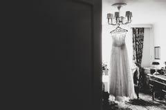 Ein Blick von hinten eine Tür auf einem weißen Kleid, das am chande hängt Stockfoto