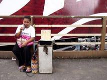 Ein blinder Sänger führt an einer Fußbrücke durch, um Geld zu erwerben Stockbild