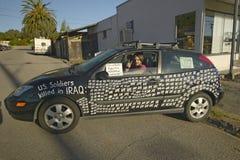 Ein blinkender Protestor der Frieden kennzeichnen innen sein Auto Stockfotos
