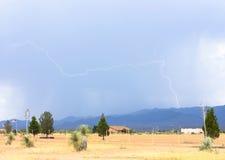 Ein Blitz über einer ländlichen Nachbarschaft Lizenzfreie Stockfotografie