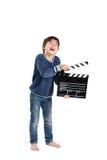Ein Bloßfuß-Junge, der clapperboard halten lacht Stockfotografie