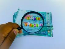 Ein Block von BuchstabeReisekosten, Währung, Lupe mit einem weißen Hintergrund stockfotos