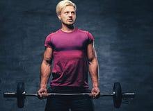 Ein blonder, athletischer Mann kleidete in einer roten Sportkleidung hält Barbe an Stockbild